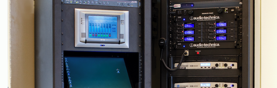 AMX touch panel with A/V equipment in racks